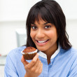 Close-up of a young businesswoman eating a muffin — Stock Photo