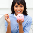 Royalty-Free Stock Photo: Smiling businesswoman saving money in a piggybank