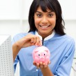 Royalty-Free Stock Photo: Assertive ethnic businesswoman saving money in a piggybank