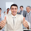 Attractive businessman and his team with thumbs up — Stock Photo