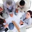High angle of multi-ethnic architects studying blueprints — Stock Photo #10290735