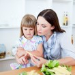 Dissatisfied little girl eating vegetables with her mother - Stock Photo