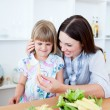 Smiling little girl eating vegetables with her mother - Stock Photo