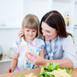 Smiling little girl eating vegetables with her mother — Stock Photo