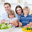 Cheerful young family cooking together — Stockfoto