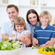 Cheerful young family cooking together - Stock Photo