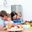 Jolly young family cooking together - Stock Photo