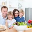 Smiling parents and their children preparing dinner together — Stock Photo