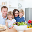 Smiling parents and their children preparing dinner together - Stock Photo