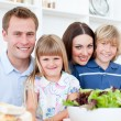 Attentive parents and their children cooking together in the kit — Stock Photo #10290968