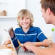 Cute boy having breakfast while his father using a laptop — Stock Photo #10290982