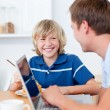 Smiling boy having breakfast while his father using a laptop — Stock Photo #10290984