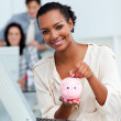 Smiling businesswoman saving money in a piggy-bank — Stock Photo #10291233