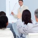 Senior businessman asking a question at a presentation — Stock Photo