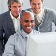 Positive businessmen helping their colleague at a computer — Stock Photo #10291418