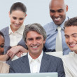 Stock Photo: Smiling Multi-ethnic business group using a laptop