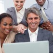 A business team showing ethnic diversity using a laptop - Stock Photo