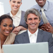Confident Multi-ethnic business team working at a laptop - Stock Photo