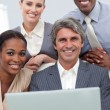 Confident Multi-ethnic business team working at a laptop — Stock Photo