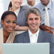 A business group showing ethnic diversity working at a laptop — Stock Photo