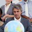 Multi-ethnic business around a terrestrial globe - Stock Photo