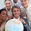 Cheerful Multi-ethnic business team showing a terrestrial globe — Stock Photo