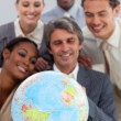 A business group showing ethnic diversity holding a terretrial g — Stock Photo