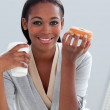 Confident businesswoman eating a donut at her desk — Stock Photo