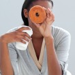 Young businesswoman eating a donut at her desk — Stock Photo