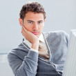 Portrait of a young businessman getting bored at work - Stock Photo