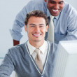 Two attractive businessmen working at a computer — Stock Photo