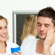 Man putting cream on his face with her wife — Stock Photo