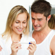 Happy woman and frightened man examining a pregnancy test - Stock Photo
