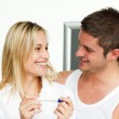 Happy couple holding a pregnancy test looking each other — Stock Photo