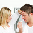 Worried woman examining a man with a termomether - Stock Photo