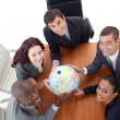 Stock Photo: High Angle of smiling team holding a globe. Global business