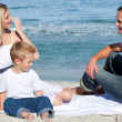 Smiling parents with their son sitting on the sand — Stock Photo #10292197