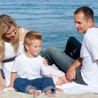 Stock Photo: Happy parents with their son sitting on sand