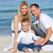 Portrait of cheerful parents with their son sitting on the sand — Stock Photo #10292200