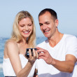 Enamored couple looking at holiday photograph — Stock Photo