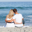 Affectionate couple sitting on the sand at the beach - Stok fotoğraf