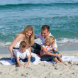 Happy family playing on the sand - Stock Photo