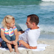Adorable little girl and her father sitting on the sand - Stock Photo