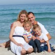 Portrait of a cheerful family sitting on the sand - Stock Photo