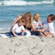Stock Photo: Attentive parents with their children sitting on the sand