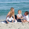 parents aimants avec leurs enfants assis sur le sable — Photo