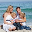 Stock Photo: Portrait of an affectionate family sitting on the sand