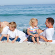Happy family sitting on the sand — Stock Photo #10292224