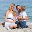 Cute children and their parents sitting on the sand — Stock Photo #10292225