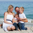Stockfoto: Happy children and their parents sitting on the sand